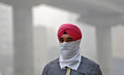 A man covers his face as he walks to work in Delhi on November 7, 2017.  Delhi's pollution levels dropped down to 'severe' level, prompting the state government to hold emergency meetings to discuss measures to combat it.  Reuters photo