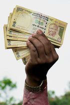 A Karnataka Youth Congress member displays the banned currency notes of Rs 500 as they observe November 8 as Black Day to mark the first anniversary of the Demonetisation announcement in Bengaluru on Wednesday. PTI