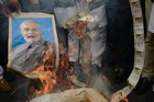 Supporters of Congress party burn old Rs 500 notes and a poster bearing the imgage of Prime Minister Narendra Modi during a protest against demonetisation and the Goods and Services Tax (GST) in Amritsar on November 8, 2017.