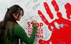 A student signs a poster to raise awareness about violence against women on International Women's Day in the University of Jammu on March 8, 2016. PTI photo