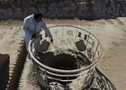In this photograph taken on February 9, 2017, Pakistani caretaker at the UNESCO World Heritage archeological site of Mohenjo Daro, Ismail Mugheri, points out a well at the site some 425 kms north of Karachi. AFP