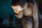 Traditional Xhosa initiate Fezikhaya Tselane, 20, applies traditional white clay for skin protection during a traditional initiation process, in a rural hut on July 11, 2017 in the Coffee Bay area in Umtata, South Africa. AFP