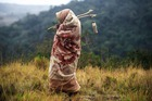 Traditional Xhosa initiate Khanyisile Mapope (R), 18 years old, walks through the bush during a traditional initiation process, in a rural hut on July 13, 2017 in the Coffee Bay area in Umtata, South Africa. AFP