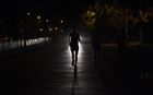 Indian runner Samir Singh (C) is silhouetted by car headlights during his run in the early morning in Mumbai. AFP
