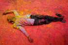 A Hindu devotee, smeared in coloured powder, takes a rest on a road during a procession for Holi celebrations in Kolkata, February 28. Reuters
