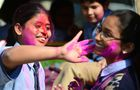 School girls play with coloured powder outside a school in Allahabad on February 28. AFP