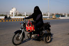 Humaira Jabeen, 32, mother of three and a family welfare worker, rides a motorbike on her way home on the eve of International Women's Day in Karachi, Pakistan, March 7. Reuters
