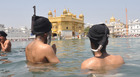 Sikh devotees take a dip in a Sarovar (sacred water tank) on the occasion of Baisakhi festival at the Golden Temple in Amritsar on April 14, 2018. Tribune photo: Sunil Kumar