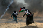 Female demonstrators run for cover from tear gas fired by Israeli forces during a protest where Palestinians demand the right to return to their homeland, at the Israel-Gaza border in the southern Gaza Strip, May 11. Reuters