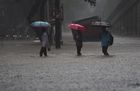 People walk through flooded streets during heavy rain showers in Mumbai on June 9, 2018. AFP photo