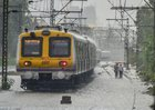A local train passes through waterlogged tracks after heavy rains in Mumbai on June 9, 2018. PTI photo