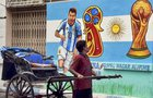 A rickshaw puller moves past a wall painted with graffiti of Argentine footballer Lionel Messi ahead of FIFA World Cup 2018, in Kolkata, June 10. PTI