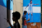 A boy paints a wall with the colours of Argentina's flag next to a man giving finishing touches to a cut-out of soccer player Lionel Messi after pasting it on a wall in an alley ahead of the FIFA World Cup, in Kolkata, June 10. Reuters