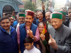 Chief Minister Virbhadra Singh with his wife and son Vikramaditya Singh ( candidate from Shimla (Rural) showing their fingers marked with ink after casting votes at a polling station at Rampur on November 9. Tribune photo