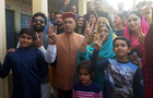 Prem Kumar Dhumal (chief ministerial candidate of BJP) with family members showing their fingers marked with ink after casting votes at a polling station at Hamirpur on Thursday. Tribune photo