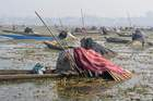 Kashmiri fishermen catch fish with harpoons in Anchar Lake on the outskirts of Srinagar on December 28. The fishermen cover their heads and part of their boats with blankets and straw as part of their tactics to catch fish in the waters of the lake. AFP