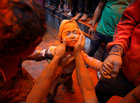 A boy gets his face smeared with vermillion powder during 'Sindoor Jatra' vermillion powder festival at Thimi, in Bhaktapur, Nepal April 15, 2017. Reuters