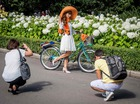 People take pictures of a participant in the 5th Lady on Bicycle annual festival in Sokolniki park in Moscow on August 6, 2017. AFP