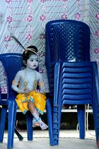 A child dressed as the Hindu deity Krishna sits on chairs during an enactment competition as part of Krishna Janmashtami celebrations in Bangalore on August 12, 2017. Krishna Janmashtami also known as Gokulashtami, is an annual Hindu festival that celebrates the birth of Krishna, the eighth avatar of Lord Vishnu. AFP photo