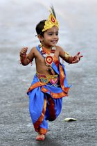 A child dressed as the Hindu deity Krishna runs around after an enactment competition as part of Krishna Janmashtami celebrations in Bangalore on August 12, 2017. Krishna Janmashtami also known as Gokulashtami, is an annual Hindu festival that celebrates the birth of Krishna, the eighth avatar of Lord Vishnu. PTI photo
