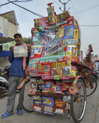 Manoj Kumar Rai, poses for photos with his rickshaw decorated with photos of Bollywood actor Amitabh Bachchan on his 76th birthday, in Jabalpur. PTI
