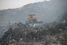 A ragpicker collects usable material as smoke rises from a garbage dump at the Bhalswa landfill site in New Delhi, on October 29, 2018. AFP photo
