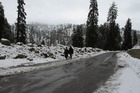 People walk on a snow covered road in Kashmir valley. Tribune Photo: Amin War