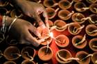 A devotee lights up a clay lamp at a makeshift Hindu temple dedicated to Hindu God Rama, as part of the preparations of the two-days celebrations for the Diwali Hindu festivalat the old Drive-Inn in Durban, on November 3, 2018. — AFP