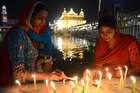 Sikh devotees light candles as they pay their respects as lights glow on the eve of 'Bandi Chhor Divas', or 'Diwali' festival, at the Golden Temple, in Amritsar on November 6. AFP