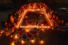 Girls light earthen lamps on a 'Rangoli' as they celebrate Diwali, the Festival of Lights, in Guwahati on November 6. AFP
