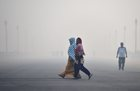 Women walk across a road engulfed in thick haze, in New Delhi, November 8. PTI