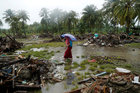 A woman holding an umbrella walks in the rain among debris after a tsunami, in Sumur, Banten province, Indonesia, on December 26, 2018. Reuters