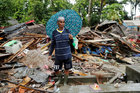 A man holding an umbrella walks through the debris of his damaged house after a tsunami in Sumur, Banten province, Indonesia, on December 26. Reuters
