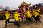 This picture taken on March 5, 2018, shows villagers carrying a shrine with a local sea deity on the beach of Fuye village on Nanri island in China's Fujian province.  AFP photo