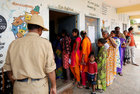 A policeman stands guard as voters wait in a queue to cast their ballot outside a polling station during Karnataka Assembly elections at a village on the outskirts of Bengaluru on May 12. Reuters