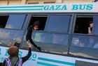 A woman hands an item to another standing in the window of a bus waiting in Khan Yunis to cross into Egypt from the Rafah border crossing in the southern Gaza Strip on May 12. AFP