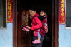 Cha Huilan, a 40-year old Lisu woman, carries her daughter in her home in Lazimi village in Nujiang Lisu Autonomous Prefecture in Yunnan province, China, March 24. Reuters