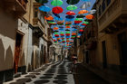 A man takes pictures under a canopy of coloured umbrellas hanging over a street in preparation for a music festival at the weekend, in Zabbar, Malta, on June 5, 2018. Reuters