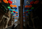 People walk under a canopy of coloured umbrellas hanging over a street in preparation for a music festival at the weekend, in Zabbar, Malta, on June 5, 2018. Reuters