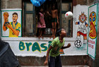 A boy plays in front an image of Brazil's soccer player Neymar painted on a wall in an alley at a slum area, ahead of the FIFA World Cup, in Kolkata, June 7. Reuters