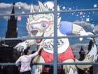 A man cleans the window of a pavilion decorated with an image of the tournament mascot Zabivaka at the World Cup Football Park on Red Square in Moscow on June 28, 2018. AFP
