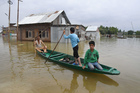 People use a boat to navigate floodwaters in Rukh Bemina, Budgam, after heavy rain in Kashmir on July 1, 2018. Tribune photo: Amin War