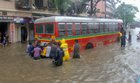 People push a public bus after it gets struck on a waterlogged street after heavy rain at Parel in Mumbai on July 9, 2018. PTI photo