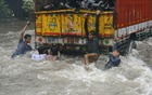 Youths try to hold onto the back of a truck as it moves along a flooded road during heavy rain showers in Mumbai on July 9, 2018. AFP photo