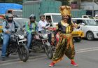 An artist dressed as 'Yamaraj' (R), the Hindu god of death, looks for motorists flouting traffic rules as part of a Road Safety Week campaign organised by traffic police in Bangalore on July 10. AFP