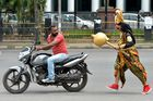 An artist dressed as 'Yamaraj' (R), the Hindu god of death, runs behind a motorist riding without a helmet as part of a Road Safety Week campaign in Bangalore on July 10. AFP