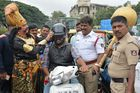 An artist dressed as 'Yamaraj' (L), the Hindu God of death, puts a helmet on a motorist during a Road Safety Week campaign organised by traffic police in Bangalore on July 10. AFP