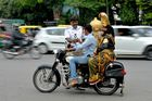 An artist dressed as 'Yamaraj', the Hindu god of death, travels with a motorist riding without a helmet while a traffic policeman gives him a rose as part of Road Safety Week campaign in Bangalore on July 10. AFP