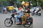 An artist dressed as 'Yamaraj', the Hindu god of death, travels with a motorist riding without a helmet, as part of a Road Safety Week campaign organised by traffic police in Bangalore. AFP