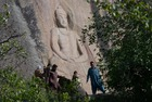 This photo taken on April 26, 2018, shows Pakistani visitors walking past the seventh-century rock sculpture of a seated Buddha carved into a mountain in Jahanabad town in the northwestern Swat Valley of Pakistan, following a restoration process conducted by Italian archaeologists after the Taliban defaced it in 2007. The Buddha of Swat, carved on a cliff in the seventh century, was dynamited by the Pakistani Taliban in 2007. Now it has been restored, a powerful symbol of tolerance in the traumatised Pakistani valley. AFP photo